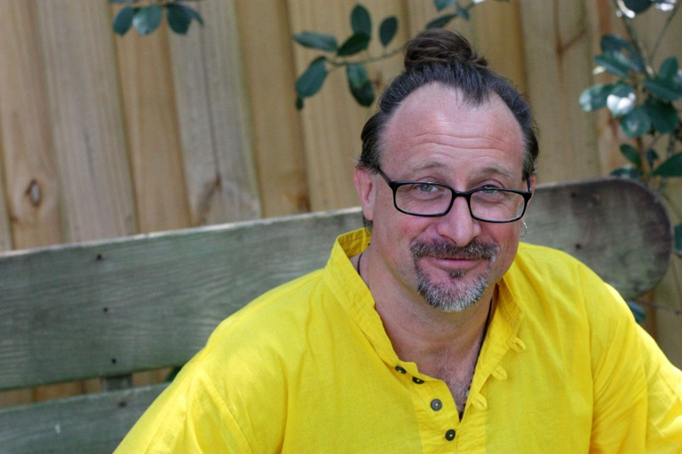 Christopher approaches the camera's gaze with a look of speculation, coy knowing, and a close-lipped smile. He is wearing a bright yellow, button-up shirt. He has pulled back his long, dark hair into a bun atop his crown, and his pinkish skin is framed by both black, rectangular glasses and a trimmed, salt & pepper goatee. He is sitting and behind him is wooden bench, fence, and a few green leaves.