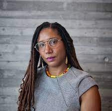 The image shows, Toya Northington. An African American woman with gold aviator glasses and a stern facial expression looking directly into the camera wearing a gray dress, with yellow earrings, and a multicolored African necklace in front of a gray concrete wall. The image was taken at the Speed Art Museum by photographer, Amber Thieneman