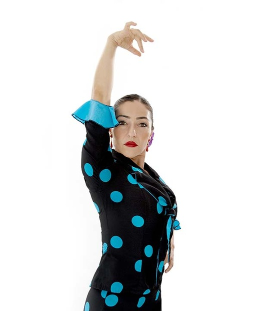 A woman with light olive toned skin, bright red lipstick, and dark brown hair pulled back tightly and neatly into a bun is staring intensely at the camera while holding a flamenco pose with her right arm overhead and her left arm on her hip. She is wearing a black dress with large, turquoise polka dots with turquoise ruffles on her sleeves.