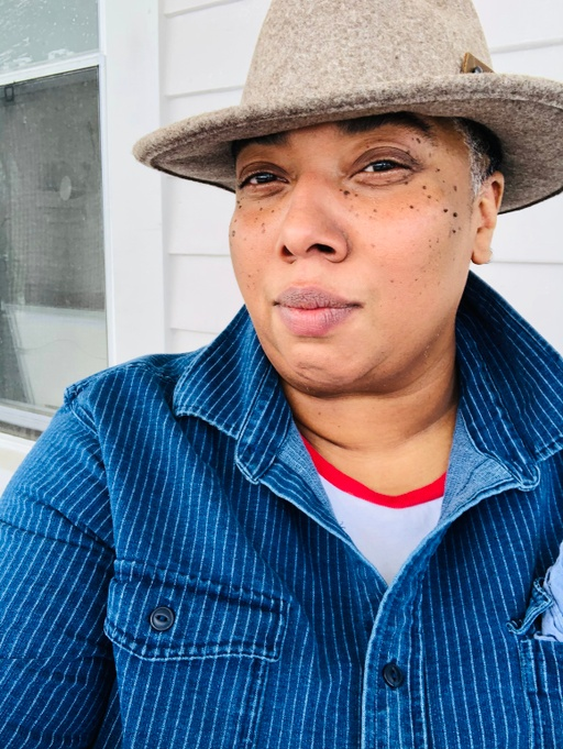 M. Carmen Lane looks directly into the camera with an inviting, all-seeing gaze. While Carmen's lips are sealed, their presence feels like a smile. They are wearing a signature, tan felted hat, a dark blue denim shirt with light pinstripes, and a white t-shirt with red collar underneath. Carmen is standing in front of a white clapboarding and a window screen is visible over their right shoulder.