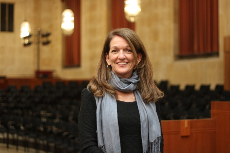 Eileen stands in an empty, well-lit theater. Her  light brown hair sweeps across both of her shoulders and her grey-blue cashmere scarf, which is wrapped around her neck. She is wearing a black long-sleeved top which blends into the background, creating a relief for her light complexion and welcoming smile. She has on two silver hoop earrings and a silver chain.