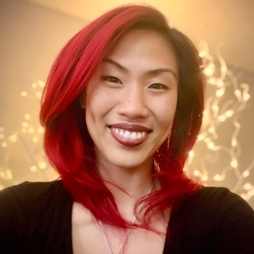 Korean woman with bright red hair. Wearing a black shirt, with a golden hue of twinkle lights behind her.