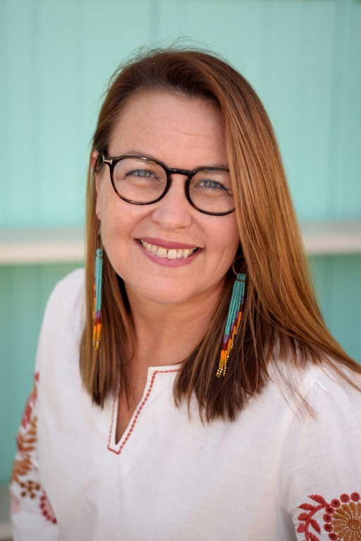 A headshot of a fair-skinned woman, smiling openly, with light brown, straight, shoulder-length hair that is swept across the side of her face. She is wearing dark-rimmed round glasses, long turquoise and orange dangling earrings, and white top with red embroidery at the sleeves. The background appears as a light aqua color and it is blurred.