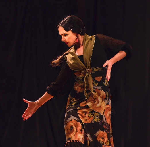 A woman dramatically strikes a flamenco pose with her right arm and hand extended diagonally to the ground and her left arm bent to her hip. She looks down over her right arm. Her dark hair is pulled loosely back into a low pony tail and she is wearing a long dress with large flowers, a black cardigan and an olive green scarf.