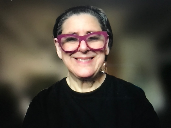 A fair skinned, older adult woman smiles at the camera. She is wearing a black, long-sleeve shirt and oversized, purple glasses. Her short, salt and pepper hair is swept back with a black headband.