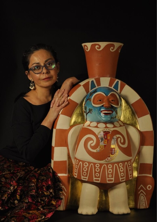 A Peruvian woman with light brown skin leans lightly against a large, ceramic sculpture made out of clay and terra-cotta depicting a Pre-Colonial figure with a blue face, wearing ornamental dress. The woman is smiling slightly with closed lips. Her black hair is pulled back and she wears black-rimmed classes and long, beaded earrings.