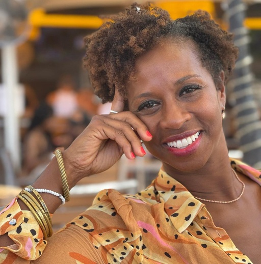 A sunlit image of a relaxed brown-skinned woman with dark, free curls that rest above her ears. Kwayera leans her head agains her hand, her arm open and propped on the back of her chair. She is dressed in a yellow patterned, gauzy shirt and is adorned in gold bracelets, earrings, and necklace and a ring on her pointer finger. She is smiling comfortably and gazes directly into the camera. The shade of her lipstick complements her bright pink manicure. The background is blurred.