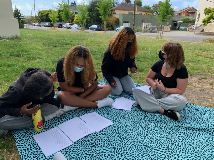 Four young folx sitting on a blue and black polka dotted picnic blanket on top of grass. Sitting on the picnic blanket L-R: Tiebe, a young person with hair in two low buns, wearing a black sweatshirt and pants, holds a yellow water bottle in her left hand while reading from 3 white papers on the ground. Gina, a young person in a black t-shirt with her hair down, reads the papers with Tiebe while sitting criss-cross. Ameena, a young person with hair down in a black long-sleeve shirt and blue jeans, sits on her knee looking at her friend. Lola, a young person in black shirt and sweatpants, looks up at Ameena. In the background there is a neighborhood with houses, trees, and cars.