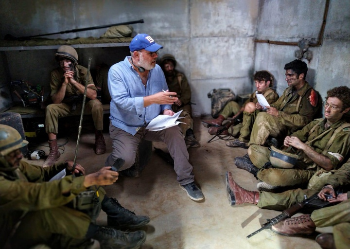 "On the set of ""Valley of Tears,"" the director sits surrounded by actors in military costume"