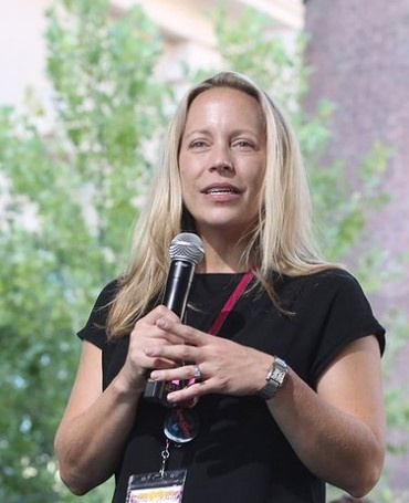A light-skinned, blonde femme holds a microphone with both hands. She is smiling, mid-delivery, and clearly engaged with an audience. She is wearing a black short-sleeved top, a silver watch, and a red lanyard with name-tag. Her long, straight, blond hair is down. A full-leaved tree is behind her as well as indistinct brick architecture.