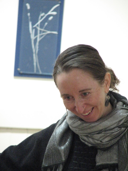 Alexandra is caught in mid-action, smiling at something below the camera's frame. Her light brown hair is pulled back, revealing her fair skin, light eyes, and large, dangly earrings. A cozy, grey scarf is wrapped around her neck under which she is wearing black layers. Behind her, a cyanotype image of grass is hanging on a white wall.