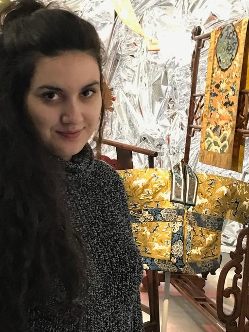An olive-skinned woman with long, brown hair, partially tied back, looks at the camera with her chin tilting slightly down. She smiles lightly. She is wearing a grey sweater and she is standing in a gallery space with a foil background in front of beautifully embroidered silk garments.