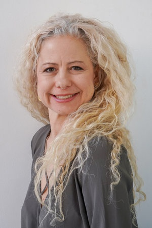 A headshot of a fair-skinned woman with long, blond, curly hair surrounding her face. She is looking over her right shoulder to the camera so that we can see her welcoming smile in full view, but her torso is turned away facing the left of the frame. She is wearing a dark grey top, complementing the light grey background.