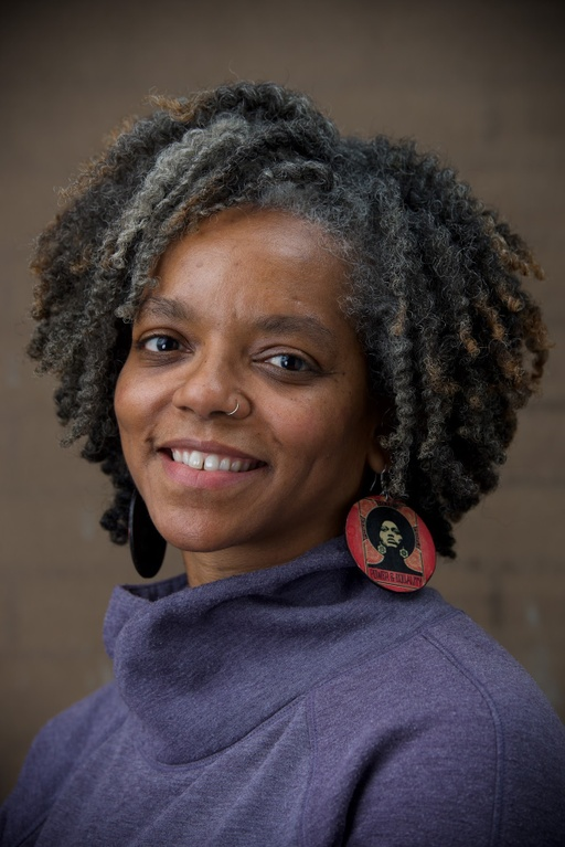 A brown skinned woman with grey and brown natural hair smiles at the camera. She is wearing a purplish-blue turtleneck sweater and large disc earrings that are red around the edges with a picture of a Black woman in the center.