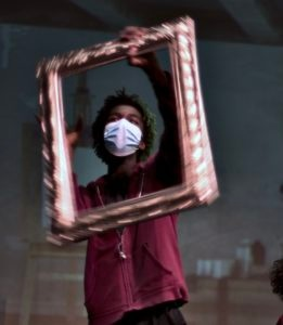 A dark skinned young person wearing a blue face mask is holding up a gold picture frame in front of their face and body.