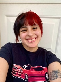 A smiling young Latinx artists with black and red hair. They are wearing a black shirt with red car, taking a selfie in front of a white door.