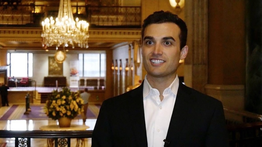 An olive skinned man with short black hair and eyebrows smiles broadly at someone past the camera to the left. He is wearing a black suit coat and a white, collared button down shirt. Behind him is an ornate, formal room with a crystal chandelier and balcony.