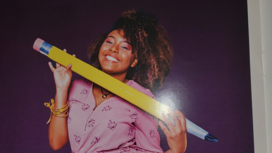 Achly embodies joy as she holds an oversized, yellow, papier-mache pencil with both hands up to her chin. Her tight curls are accented by lighter highlights and fall across her eyes, enhanced by red eyeshadow, and complementing her light brown complexion. She is wearing a pink top with a pattern of umbrella line drawings, a necklace on which a ring hangs, and a collection of yellow bracelets on her right arm. The background is dark purple.