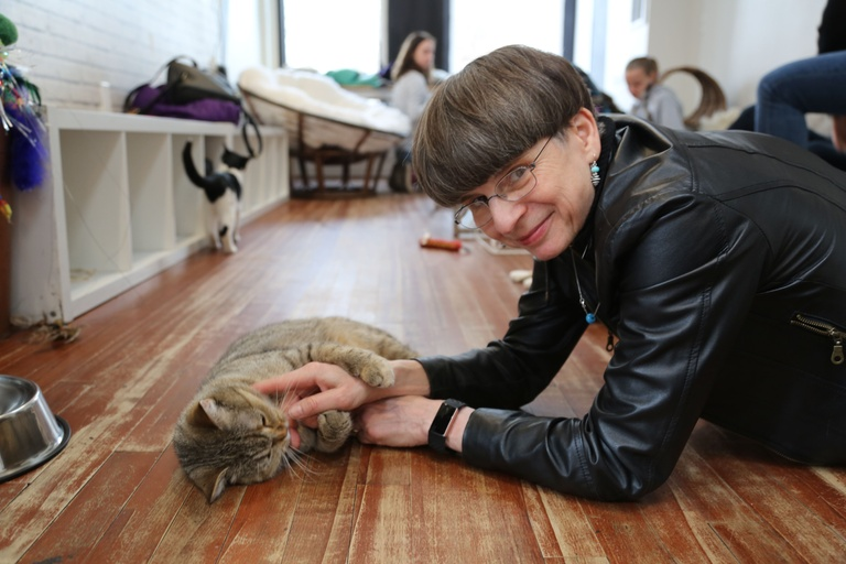 A fair-skinned woman with a brown, bowl cut and wire-rimmed glasses lies on the floor, propped up on her elbows. She is tickling a tabby cat under the chin while smiling at the camera. The cat is splayed on the floor holding her wrist. The woman is wearing a black leather jacket, a watch, and a turquoise necklace with matching, dangle earrings.