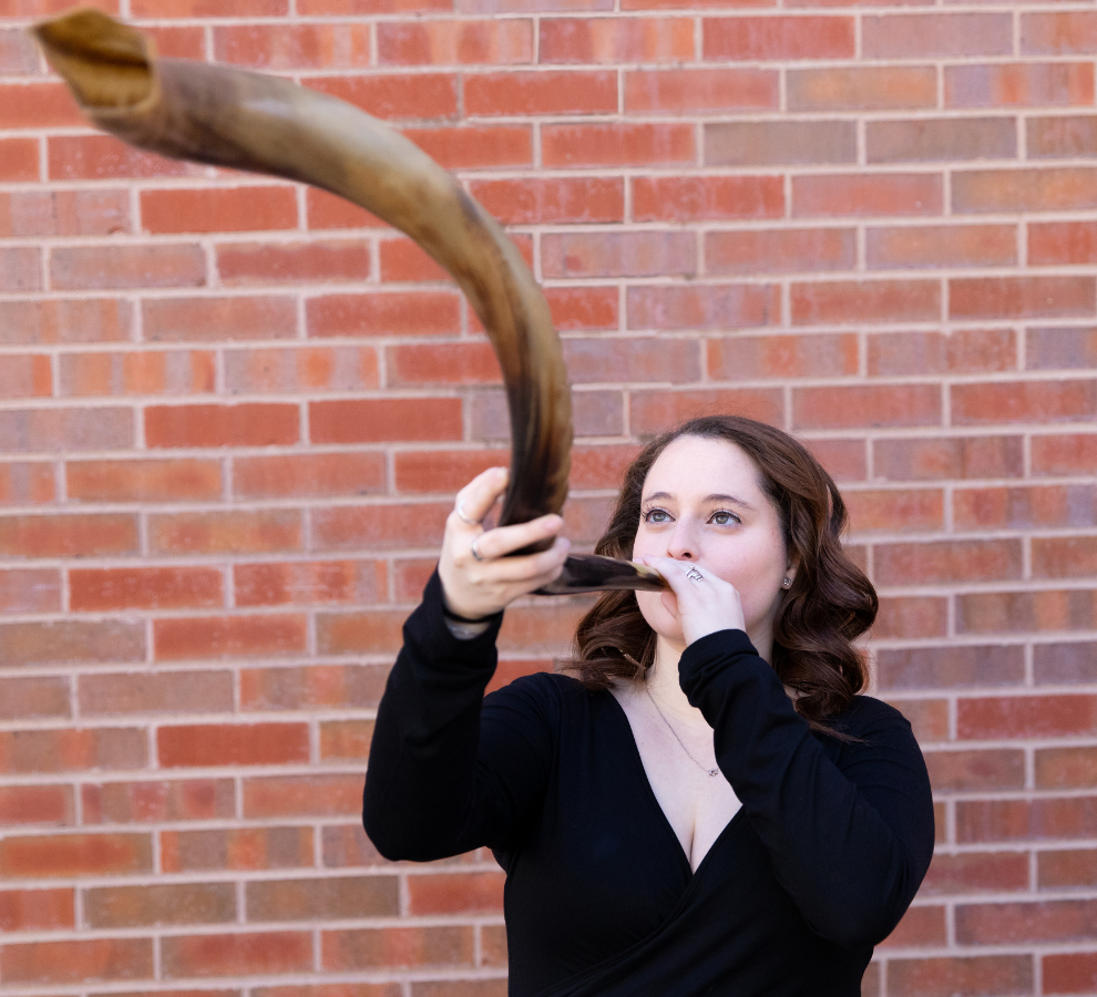 A person with shoulder length brown hair and pale skin blows a shofar