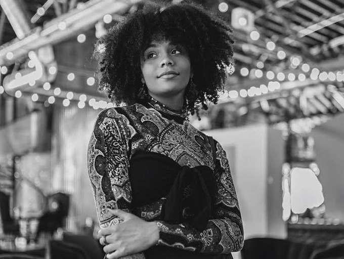 A curly-haired light brown-skinned femme gazing into the distance with a slight smirk on their face with their arms crossed. She is wearing a patterned long sleeve shirt with a high neck and a bow tied on the front. In the blurred background are lights hanging from the ceiling and a seating area. The entire photo is in Black and White.