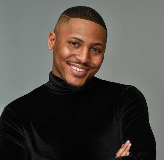 A smiling, young Black man with caramel skin and short brown hair, wearing a black turtleneck. With crossed arms posing in front of a gray background.