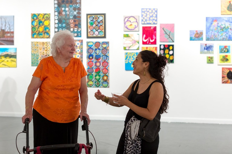 On the left is Cynthia, a light-skinned woman with white, short curly hair, wearing a bright orange shirt and black pants. She stands with support from a rollator walker while talking with a younger woman with light brown skin, a black dress and long curly brown hair pulled partially up in a bun. They are standing in the middle of a brightly lit gallery space with vibrant paintings behind them against a white wall.
