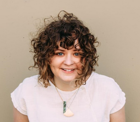 A fair-skinned woman with shoulder-length, curly brown hair smiles directly at the camera. She is wearing a white, t-shirt and two pendant necklaces and stands in front of a beige background.