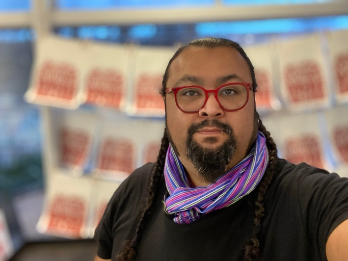 """Headshot of a light brown Mexican-American male with pulled back hair with two braids down to the chest. William has a goatee and long side burns. He is wearing two silver small hoop earrings and cherry red glasses and he has a piercing on his right nostril and bottom left lip. He is wearing a black t-shirt and a multicolored stripped """"reboso"""" or long woven scarf wrapped around his neck. The background is blurred and shows multiple screen printed posters on white paper that high light a quote by Grace Lee Boggs that says, """"The only way to survive is by taking care of one another."""""""