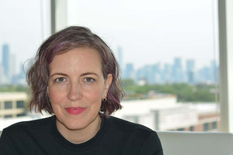 A white-skinned femme with a wavy multicolored bob half sits in front of a giant window, the Chicago skyline behind her. She has a light wash of bright pink lipstick, a black turtleneck, and the tiniest gold hoops.
