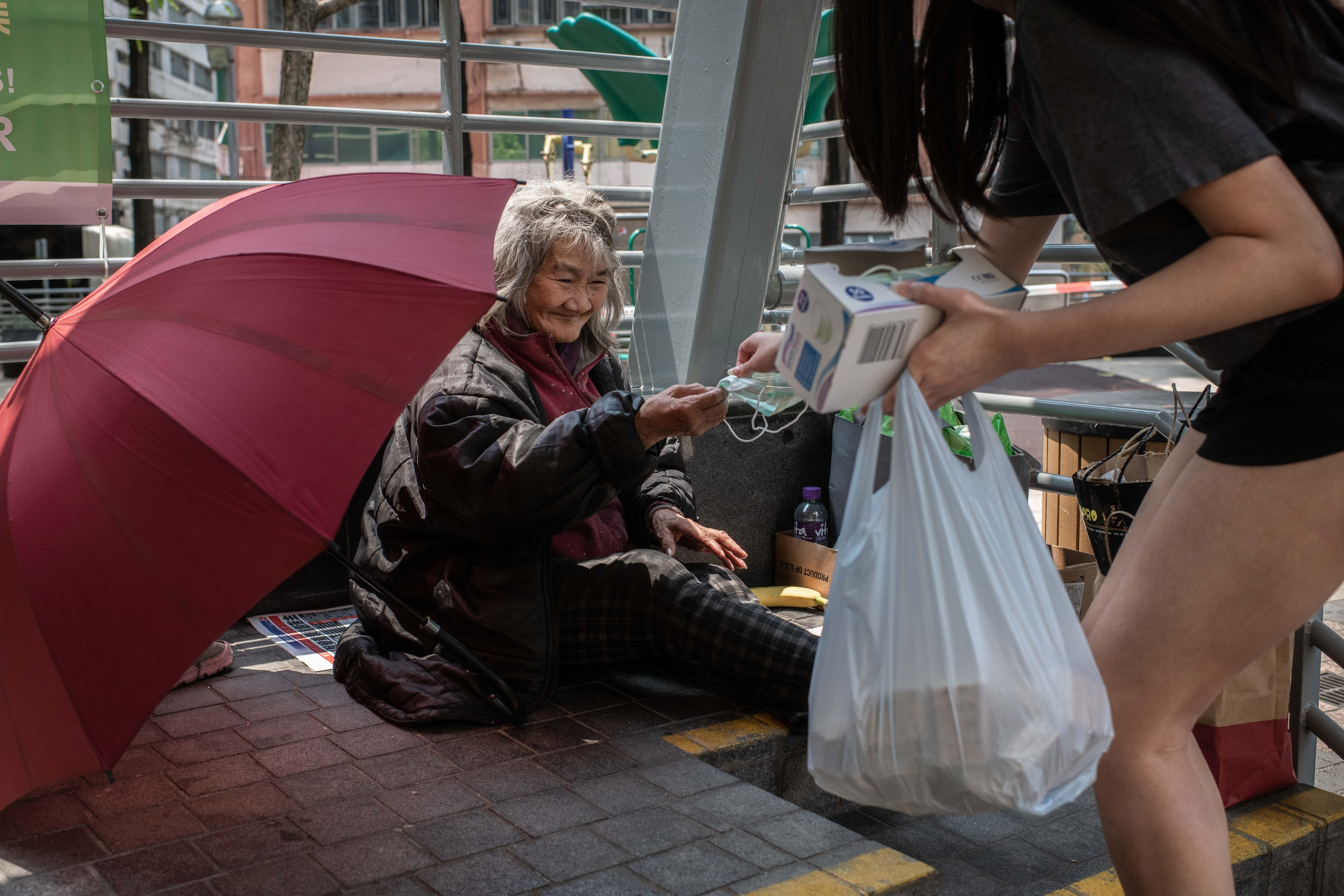 An elderly homeless woman receives a surgical mask from a volunteer as a preventive measure against the spread of Coronavirus. Photography by Ivan Abreu.