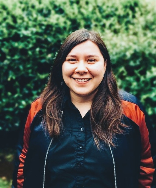Marina is standing with a big, open smile, with green foliage in the background. She has long, straight brown hair, light skin, and is wearing a black bomber jacket with an orange stripe down the sleeves, and a black button down shirt underneath.