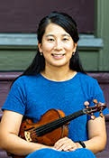Sarah is wearing a blue short sleeve dress, with black hair pulled half way up and black eyes. She is seated holding her violin at her side.