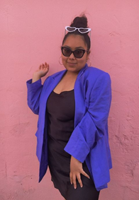A light brown young person wearing dark shades, black dress, and blue coat. They are smiling in front of a pink wall.