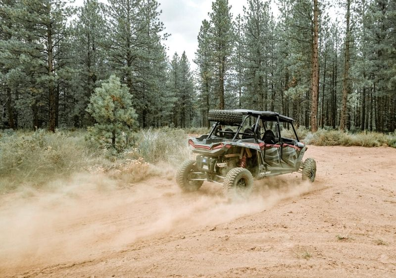 Polaris-RZR-driving-through-a-dirt-trail-in-the-forest
