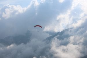 paraglider in a cloudy sky  surrounded by mountains