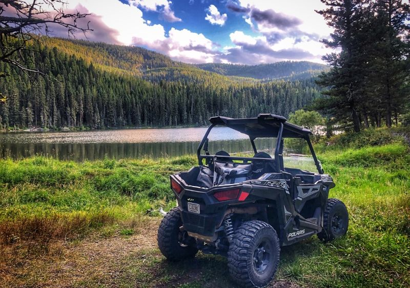 Polaris-RZR-parked-along-a-scenic-lake-surrounded-my-mountains