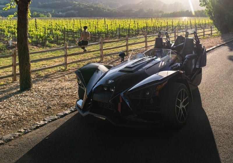 Polaris Slingshot parked along a winery road while guest overlooks the winery at sunset