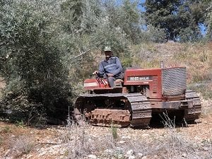 A farmer working in the Olive grove poses for a photo, Sierra Magina, Spain