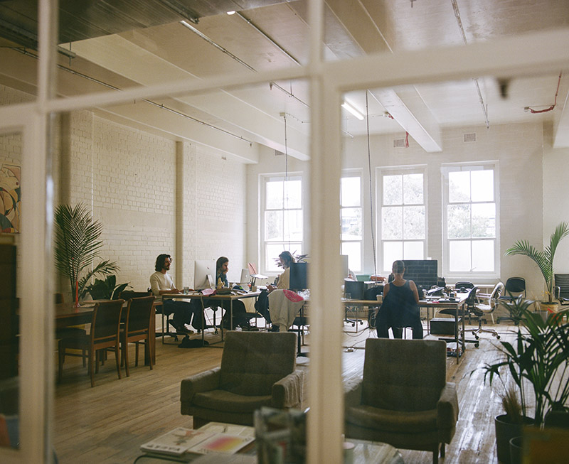 Several desks, people and plants can be seen through large windows