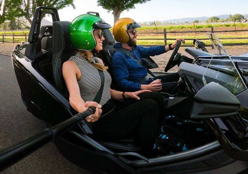 side view of guests riding in a Polaris Slingshot driving-through Missouri wine country