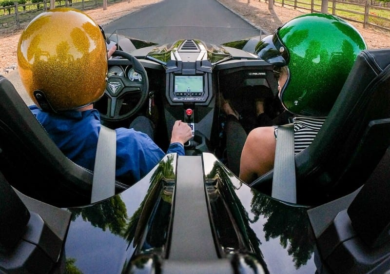 back view of guests riding in a Polaris Slingshot while driving through Missouri wine country