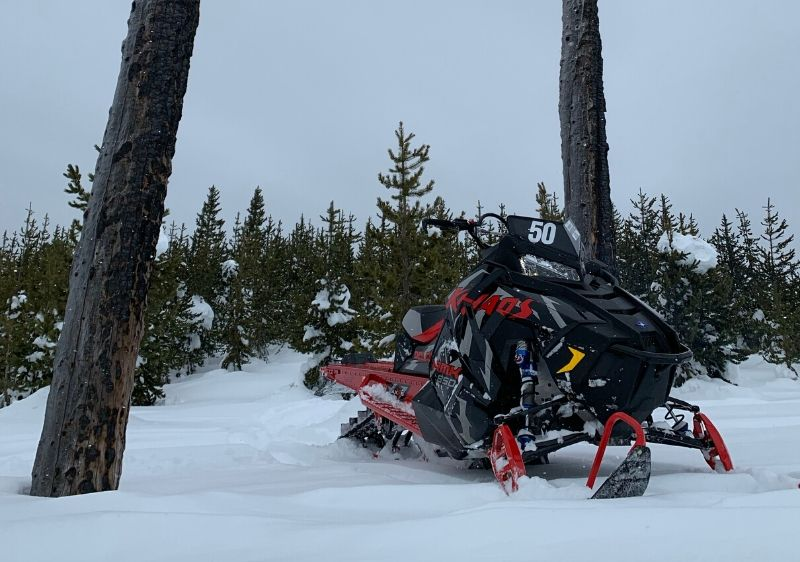 Polaris-RMK-Snowmobileparked-between-tall-trees