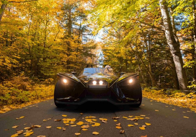 frontal-view-of-a-Polaris-Slingshot-driving-down-the-road-in-mid-fall