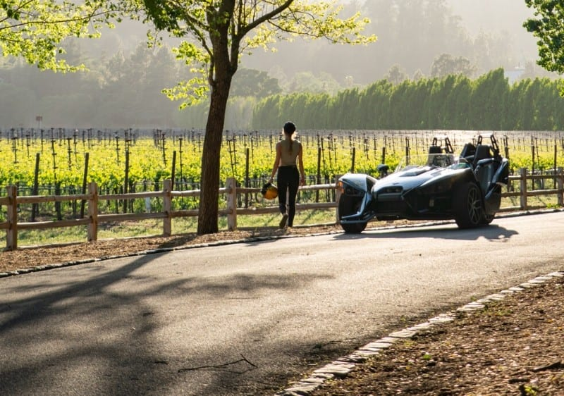 guest overlooking a winery standing next to a parked Polaris Slingshot