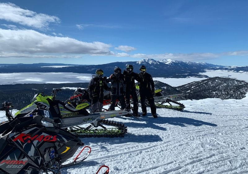 guests-posting-in-front-of-a-scenic-overlook-with-their-snowmobiles