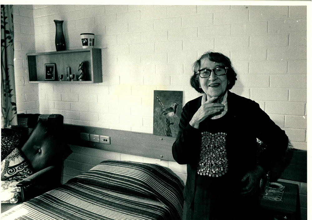 A photo of a resident in her room at Sambell lodge an aged care facility. She is smiling at the camera.