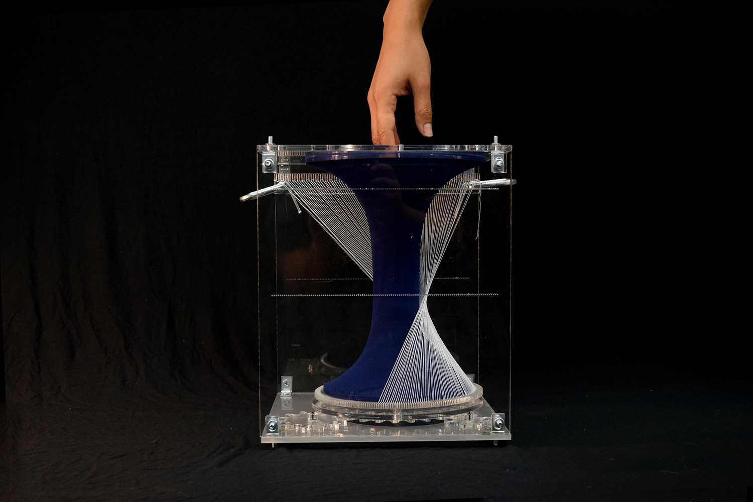 hand hovering over textile form through a hole in one face of the vertical acrylic box