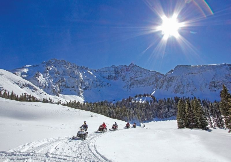 snowmobile tour group through San Juan Mountains