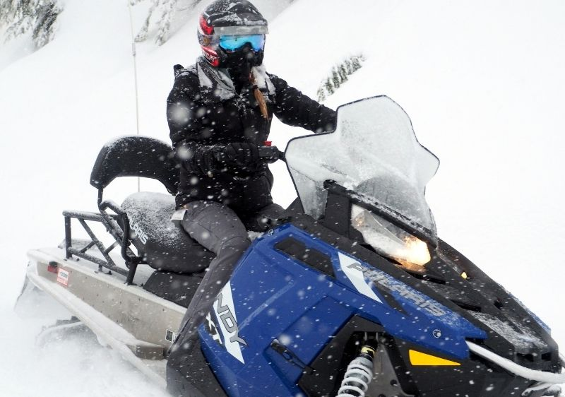 guest driving a snowmobile